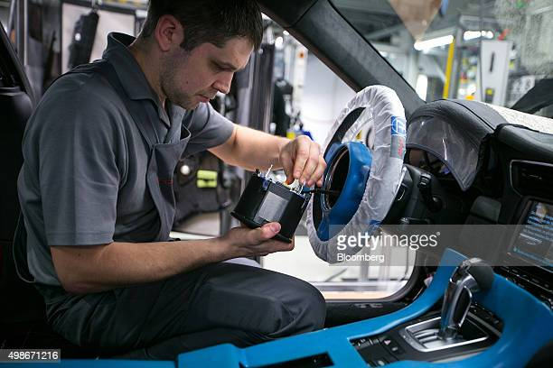 An employee fits an airbag unit to the steering wheel of a Porsche 911 luxury automobile on the assembly line at Porsche AG's factory operated by...