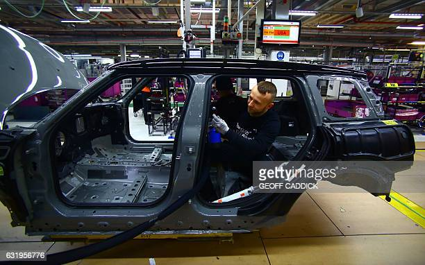 An employee fits the wiring loom to a Mini at the BMW Mini car production plant in Oxford west of London on January 17 2017 / AFP / GEOFF CADDICK