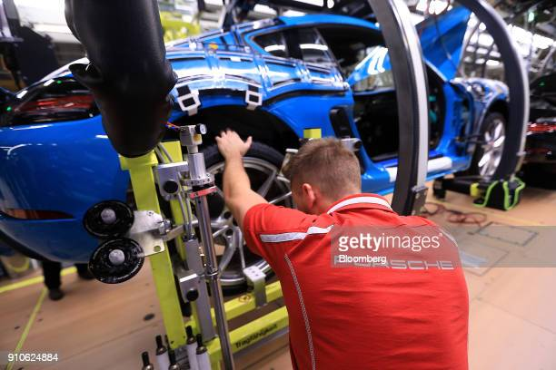 An employee fits tires on a Porsche 718 Cayman luxury automobile on the production line inside the Porsche AG luxury automobile factory in Stuttgart...