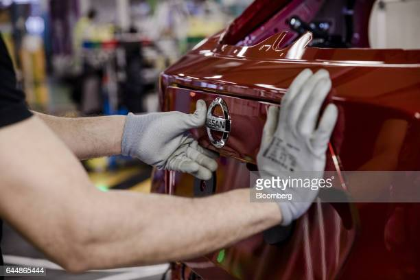 An employee fixes a badge to Nissan Micra automobile on the assembly line inside the Renault SA factory in Flins France on Thursday Feb 23 2017...