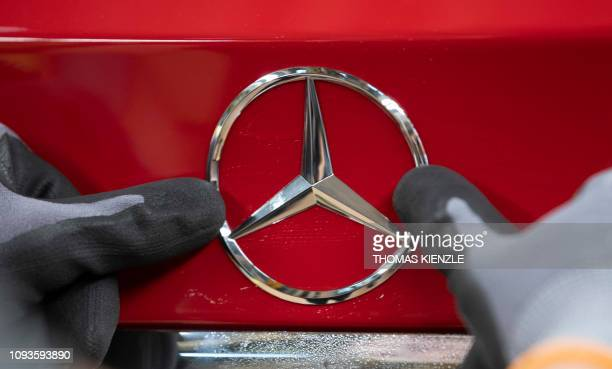 An employee fixes a Mercedes logo on a Mercedes Benz A Class on the assembly line at the Daimler AG factory in Rastatt southwestern Germany on...