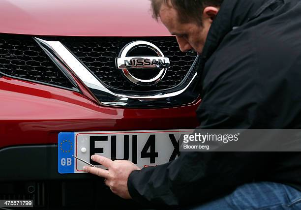 An employee fixes a new 2014 vehicle license registration plate to the bumper of a Nissan Micra automobile produced by Nissan Motor Co in this...