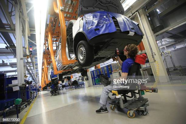 An employee fixes a protective underbody shield to a Volkswagen Transporter T6 panel van inside the Volkswagen AG factory in Hanover Germany on...