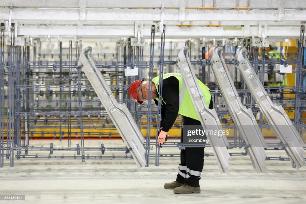 An employee fixes aluminum parts to a flight bar to be dipped into cleaning and anodising tanks at the Sapa SA aluminum plant in Bedwas, U.K., on Wednesday, Oct. 4, 2017. After being closed for three years due to a weak market, Sapa's aluminum plant in south Wales reopened to supply lightweight parts for automakers such as London Electric Vehicle Co., the maker of black cabs. Photographer: Luke MacGregor/Bloomberg via Getty Images