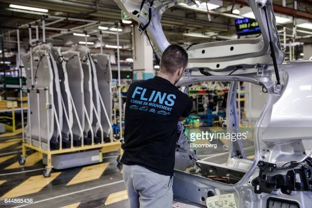 An employee fixes cables to the boot of a Renault Clio automobile on the assembly line inside the Renault SA factory in Flins France on Thursday Feb...