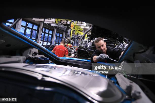 An employee fixes engine hood sealing on a Porsche 718 Cayma luxury automobile on the production line inside the Porsche AG factory in Stuttgart...