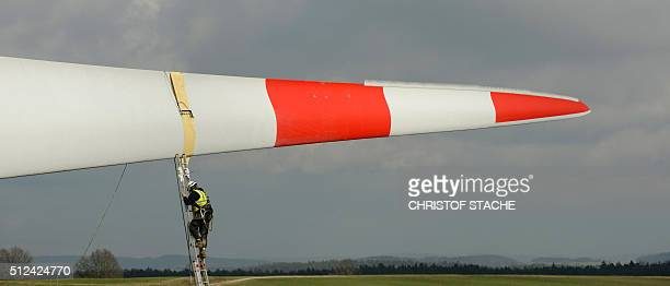 An employee fixes ropes at a rotor blade of a wind turbine prior the installation of the rotor blades near the small Bavarian village of Sindersdorf...