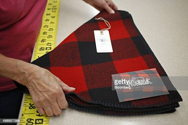 An employee folds a wool Christmas tree skirt at the Woolrich Inc woolen mill in Woolrich Pennsylvania US on Wednesday Nov 4 2015 Woolrich the...