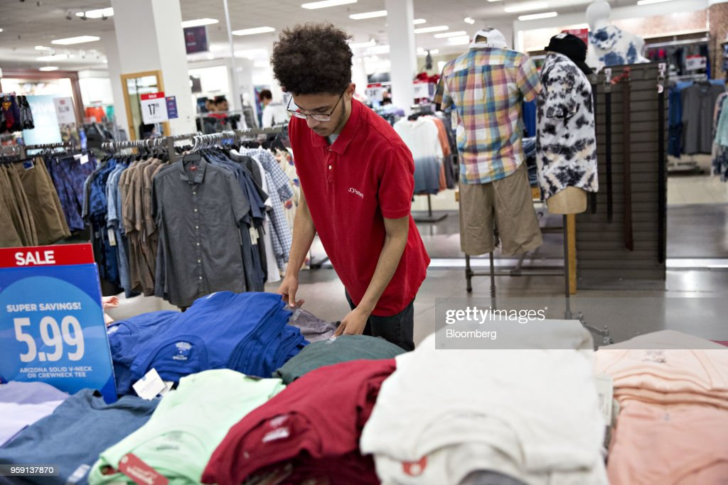 An employee folds clothes inside a J.C. Penney Co. store in Peoria, Illinois, U.S., on Saturday, May 12, 2018. J.C. Penney Co. is scheduled to release earnings figures on May 17. Photographer: Daniel Acker/Bloomberg via Getty Images