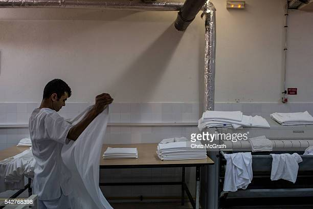 An employee folds sheets in the laundry of the closed Imperial Marhaba Hotel on June 24 2016 in Sousse Tunisia The Imperial Marhaba hotel was the...