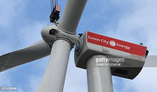 An employee follows the assembly of the rotor blades of a wind turbine near the small Bavarian village of Sindersdorf near Nuremberg southern Germany...