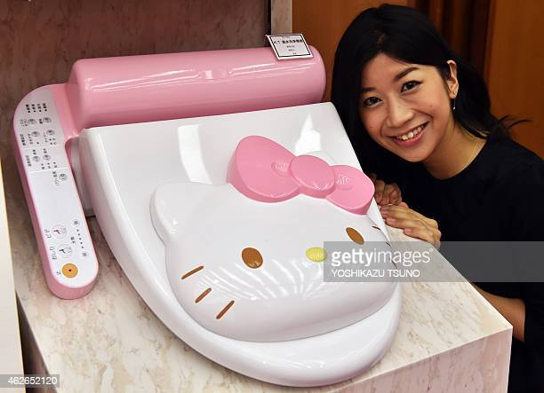 An employee for Japanese character goods maker Sanrio displays a prototype model of a Hello Kitty branded toilet seat at Sanrio's headquarters in...