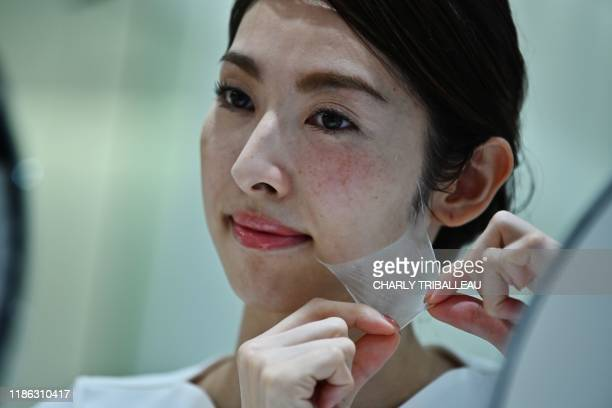 TOPSHOT An employee for Japanese cosmetics company Kao removes a super thin transparent layer after using a palmsized diffuser on her face during a...