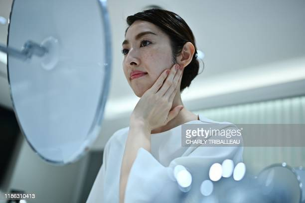 An employee for Japanese cosmetics company Kao takes part in a product demonstration of a palmsized diffuser for her face in Tokyo on December 4 2019...