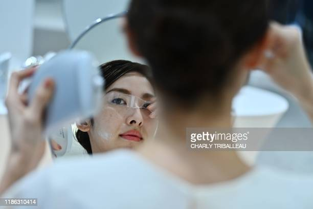 An employee for Japanese cosmetics company Kao uses a palm-sized diffuser on her face, during a product demonstration in Tokyo on December 4, 2019. -...