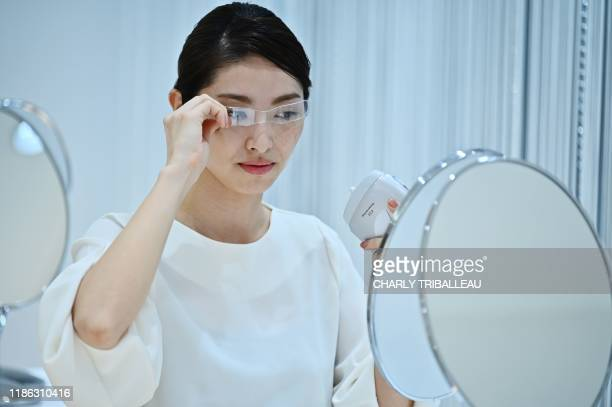 An employee for Japanese cosmetics company Kao uses a palmsized diffuser on her face during a product demonstration in Tokyo on December 4 2019 Kao...