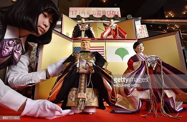 CORRECTION An employee for Japanese doll maker Kyugetsu displays sets of 'hina' dolls with likenesses of US President Donald Trump and Tokyo Governor...