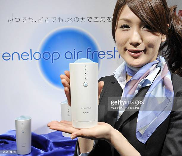 An employee for Japanese electronics giant Sanyo displays the company's new portable air purifier called 'eneloop air fresher' which has a 'virus...