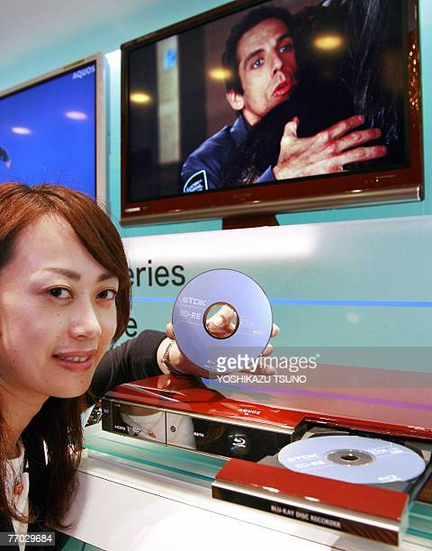An employee for Japanese electronics giant Sharp displays the company's new Bluray Disc recorder Aquos Bluray BDAV10 which can record and play a...