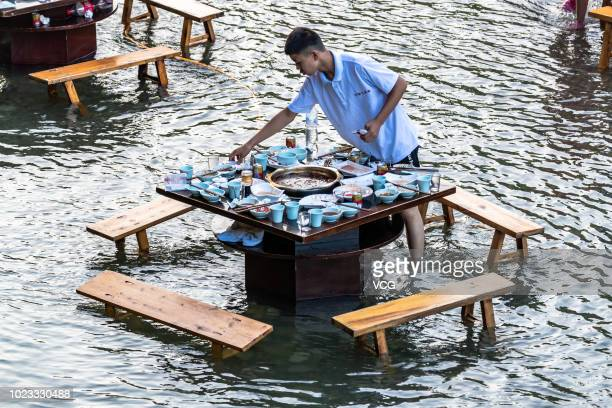 An employee from a hot pot restaurant standing in water cleans up a table at a scenic spot of Mount Jinfo on August 21 2018 in Chongqing China...
