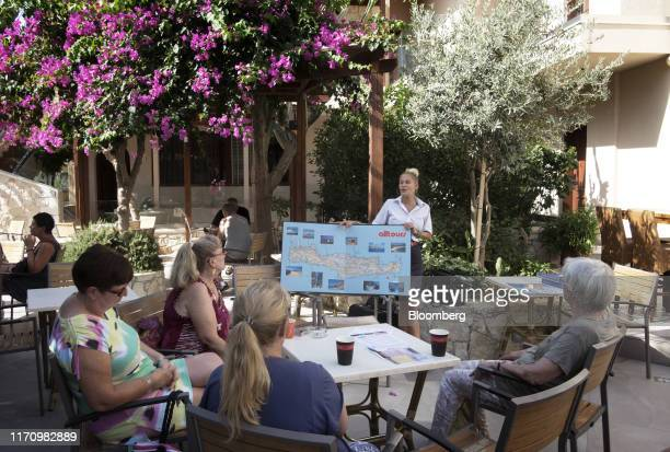 An employee from Alltours gives a tour brief in German to tourists at Cactus hotel, in Hersonissos, on the island of Crete, Greece, on Tuesday, Sept....