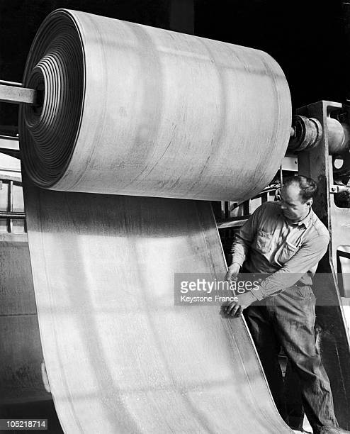 An Employee From The American Rubber Company Inspecting The Consistency Of A Roll Of Rubber After It Has Been Dried In Passaic New Jersey Between...