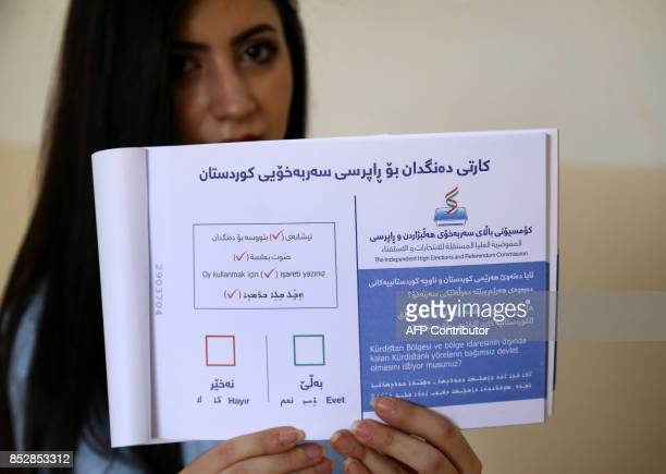 An employee from the Independent High Electoral Referendum Commission holds a voting ballot book at a voting station ahead of tomorrow's planned...