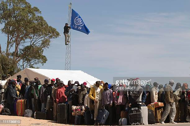 An employee from the Internationnal Organisation for Migration puts up a flag as Ghanaian refugees line up in a field as they wait to board buses to...
