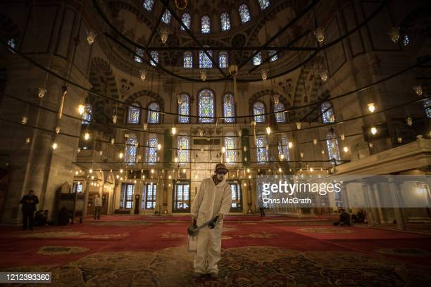 An employee from the Istanbul Municipality disinfects Fatih Mosque ahead of evening prayers to prevent the spread of the COVID-19, coronavirus on...