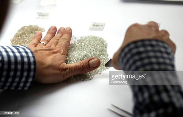 An employee gathers a pile of uncut diamonds ready for grading in this arranged photograph at the De Beers office in London UK on Friday Nov 16 2012...
