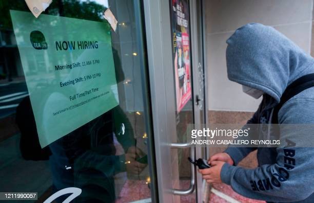 An employee gets keys to open a restaurant which is hiring in Arlington, Virginia, on May 6, 2020. - The April US employment report, due out May 8,...