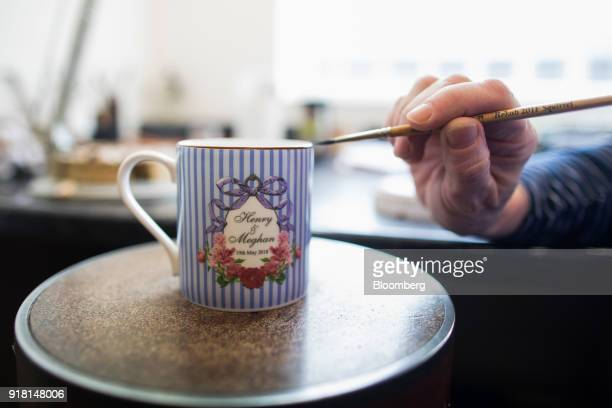 An employee gilds a china mug commemorating the wedding between Henry Windsor and Meghan Markle at Halcyon Days Ltd's factory in StokeonTrent UK on...