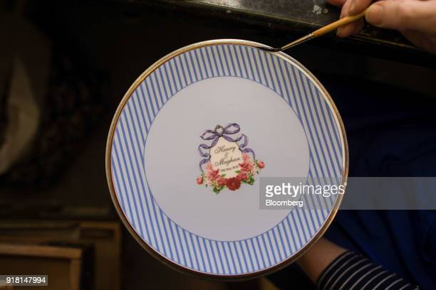 An employee gilds a china plate commemorating the wedding between Henry Windsor and Meghan Markle at Halcyon Days Ltd's factory in StokeonTrent UK on...