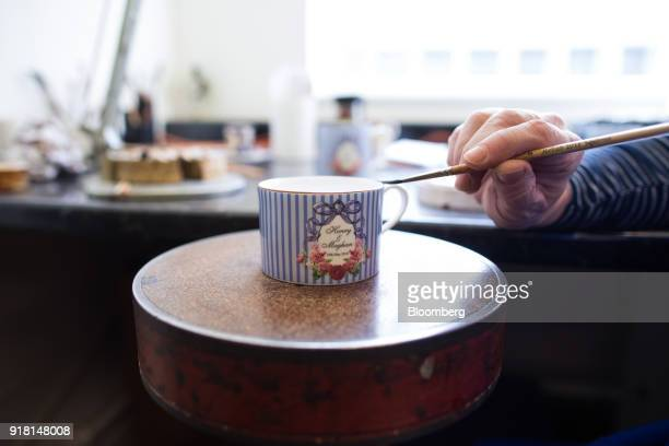 An employee gilds a china teacup commemorating the wedding between Henry Windsor and Meghan Markle at Halcyon Days Ltd's factory in StokeonTrent UK...