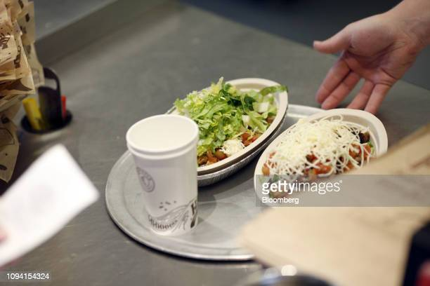 An employee gives a customer burrito bowls on a tray at a Chipotle Mexican Grill Inc restaurant in Louisville Kentucky US on Saturday Feb 2 2019...