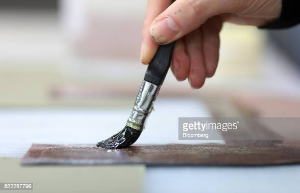 An employee glues a section of leather for use on a Kempton canvas tote bag at the Alfred Dunhill Ltd London Leather Workshop in London UK on Tuesday...