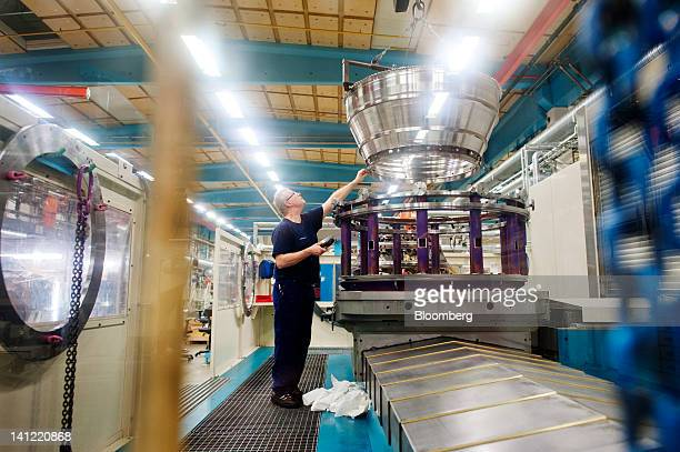 An employee guides an aircraft engine component into position during manufacture at the Volvo Aero factory a division of Volvo AB in Trollhaettan...