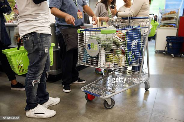 An employee guides customers on the opening day of the 365 by Whole Foods Market store in the Silver Lake neighborhood of Los Angeles California US...