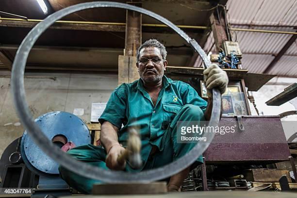 An employee hammers a metal ring an Ishwar Engineering Co factory in Mumbai Maharashtra India on Saturday Feb 7 2015 The International Monetary Fund...