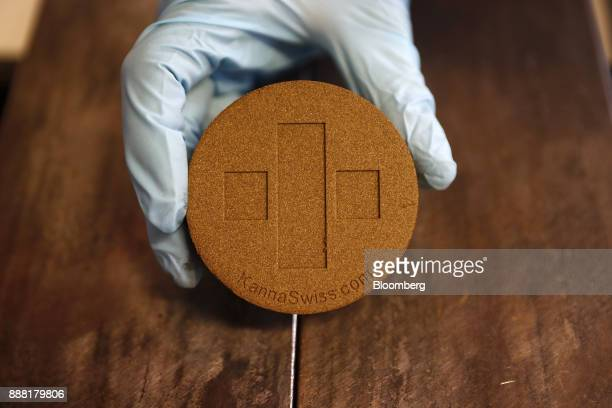 An employee handles a pressed legal hash brick which is stamped with the company logo inside the production area at KannaSwiss GmbH in Koelliken...