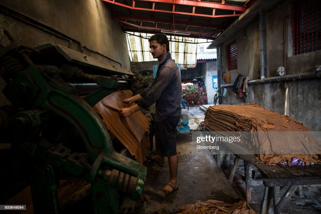 An employee handles a sheet of leather on a machine at the Sheong Shi Tannery in Kolkata, West Bengal, India on Tuesday, Dec. 26, 2017. India's manufacturing sector grew in December as the Nikkei India Manufacturing Purchasing Managers' Index (PMI) rose to 54.7 from 52.6 in November, with a number above 50 indicating expansion. Photographer: Taylor Weidman/Bloomberg via Getty Images