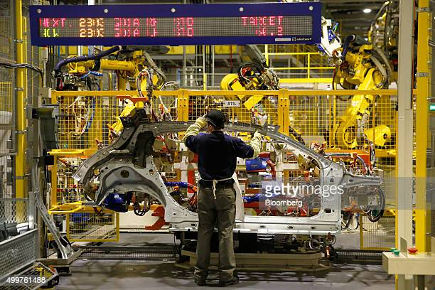 An employee handles a side panel of an Infiniti Q30 automobile on the production line at the Nissan Motor Co production plant in Sunderland UK on...