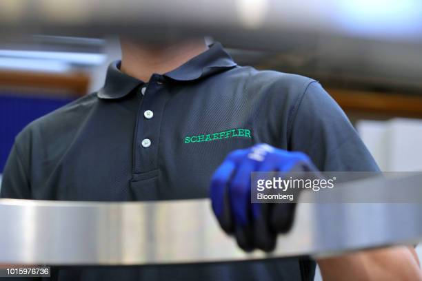 An employee handles a wind turbine bearing housing ring on the production line inside the Schaeffler AG machine tool 40 factory in Hoechstadt Germany...