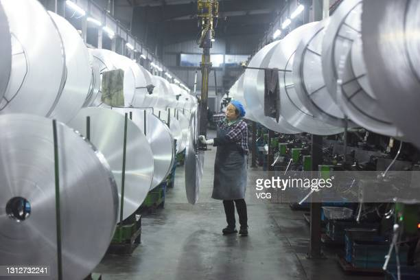 An employee handles aluminum material for aluminum electrolytic capacitor at Ao-Xing workshop on April 16, 2021 in Hangzhou, Zhejiang Province of...