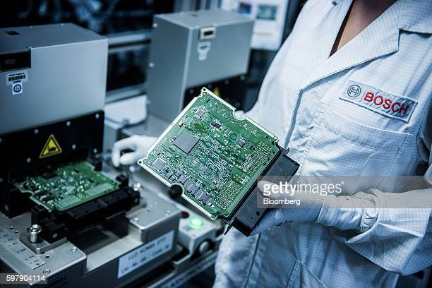 An employee handles an engine control module on the assembly line inside the Robert Bosch GmbH manufacturing plant in Hatvan Hungary on Tuesday...