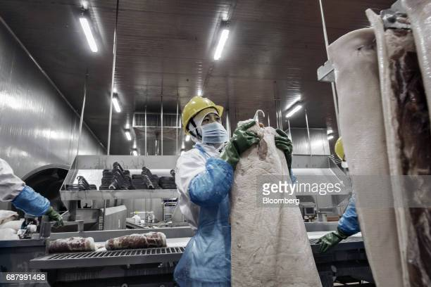 An employee handles an imported Smithfield Foods Inc pork belly on a production line that processes the pork into bacon at the WH Group Ltd facility...
