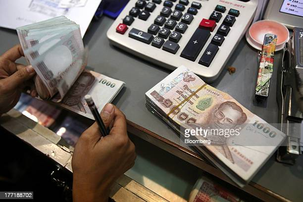 An employee handles bundles of Thai onethousand baht banknotes at a Super Rich 1965 Co currency exchange store in Bangkok Thailand on Thursday Aug 22...