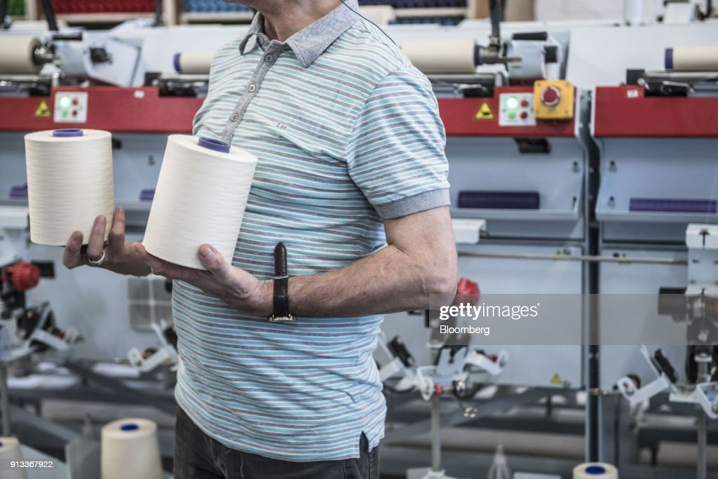 An employee handles spools of cotton yarn inside English Fine Cottons at Tower Mill, in Manchester, U.K., on Friday, Jan. 26, 2018. The restoration of Tower Mill and the launch of English Fine Cottons as the only commercial cotton spinner in the UK, has brought an industry back to its spiritual home in the North West of England. Photographer: Matthew Lloyd/Bloomberg via Getty Images