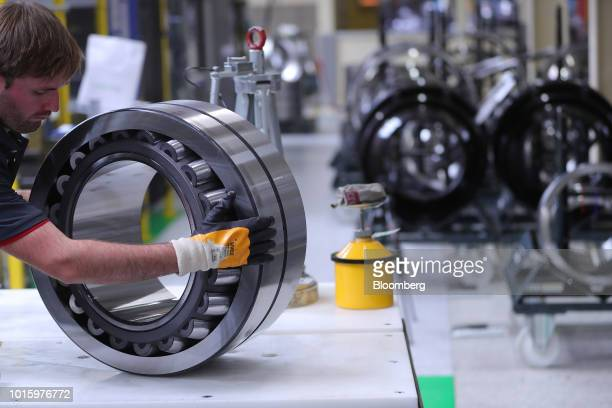 An employee handles steel roller bearings on the assembly line inside the Schaeffler AG factory in Schweinfurt Germany on Tuesday July 3 2018...
