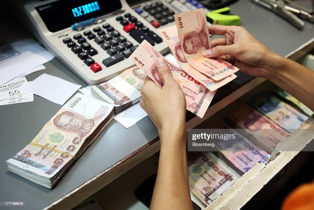 An employee handles Thai one-hundred baht banknotes as banknotes of other denominations sit inside a drawer at a Super Rich 1965 Co. currency exchange store in Bangkok, Thailand, on Thursday, Aug. 22, 2013. Thailand's baht fell to the weakest level since August 2010 after Federal Reserve minutes showed officials support a cut in stimulus this year should the U.S. economy improve. Photographer: Dario Pignatelli/Bloomberg via Getty Images